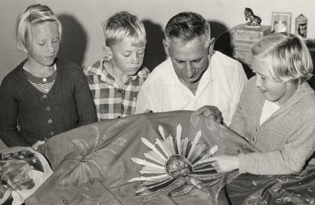 Pat Sullivan showing his embroidery to his family. Picture: Australian War Memorial