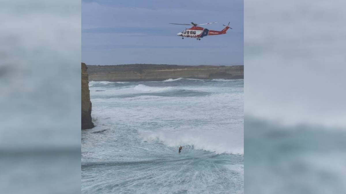 Mission: HEMS4 winches the third lifesaver to safety from the heavy seas near Port Campbell on Sunday where two men died trying to save a tourist. Picture: Ian McCauley